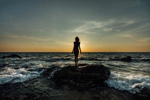 woman standing on a rock in the ocean